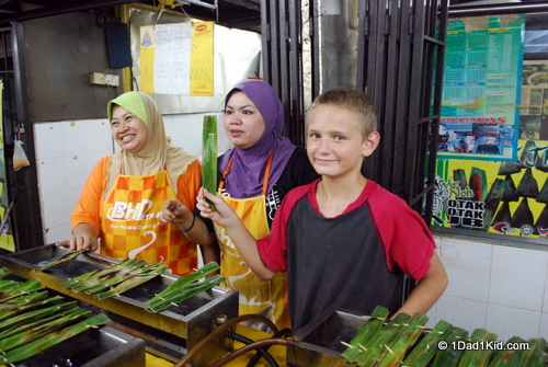 Tigger posing with some Malay women preparing otay otay (grilled fish paste cooked in palm leaves)